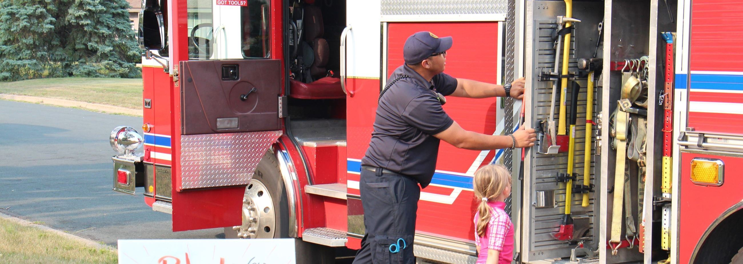 Firefighter and kid explore the fire truck